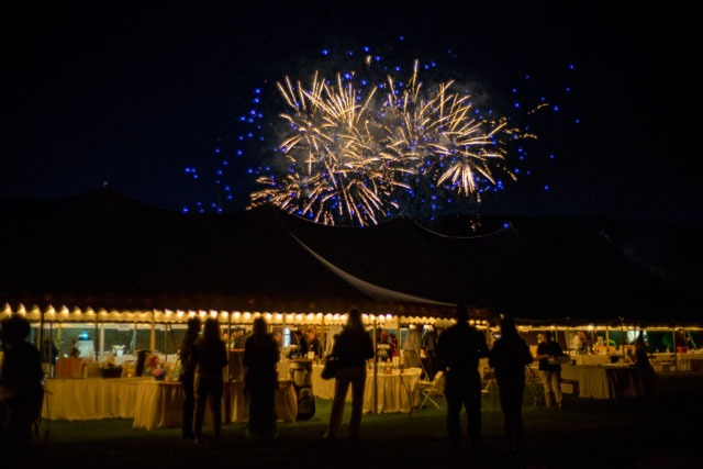 Fireworks lighting up the night sky over a tent during the Savor the Summer event